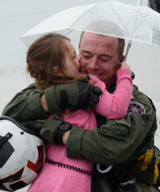 An aviator hugs his daughter after returning home. by Flickr user Official U.S. Navy Imagery