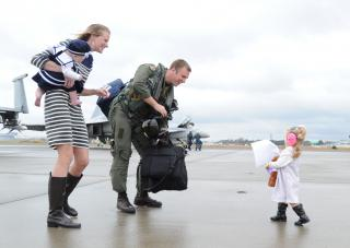 An aviator is welcomed home by his daughter. by Flickr user Official U.S. Navy Imagery