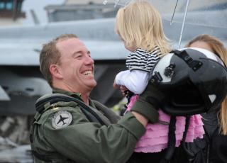 An aviator picks up his daughter after returning home. by Flickr user Official U.S. Navy Imagery