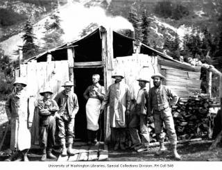 Mining crew, including Lawrence Lindsley, in front of miners' cabin, Ptarmigan Park, near Esther Mines, 1900 by Flickr user IMLS DCC